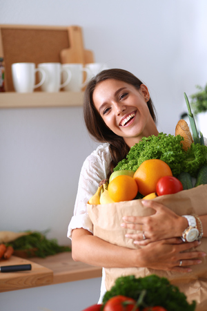 Young woman holding grocery shopping bag with vegetables . Фото со стока - 43777371