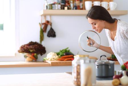 estufa: Joven mujer de pie junto a la estufa en la cocina.
