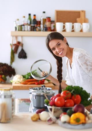 Jeune femme debout près du poêle dans la cuisine. Banque d'images - 43778433