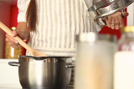 木のスプーンが付いている台所で炊事婦は。