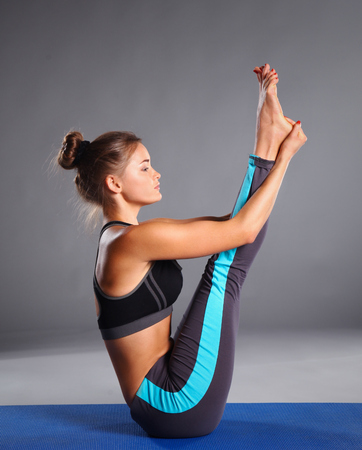estiramientos: Retrato de la muchacha del deporte que hace yoga ejercicio de estiramiento.