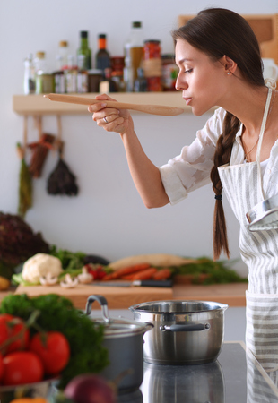 Cooking woman in kitchen with wooden spoon.