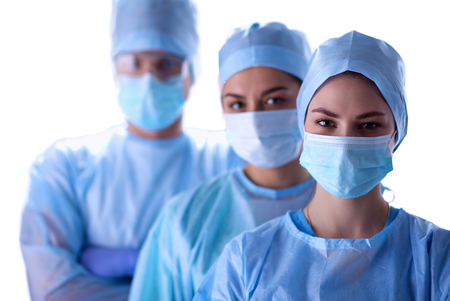 Surgeons team, man and woman wearing protective uniforms,caps and masks.