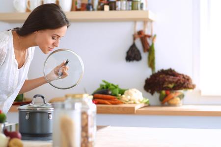 キッチンでストーブのそばに立っている若い女性。 写真素材