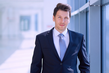 business contact: Portrait of businessman standing near window in office .