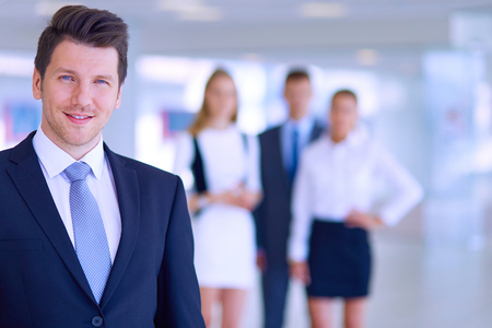 executive team: Portrait of young businessman in office with colleagues in the background .