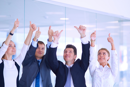 happy business team: Happy business team showing thumbs up in office .