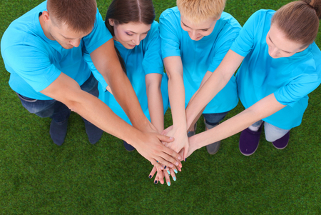unanimous: People joining their hands  on green grass . Stock Photo