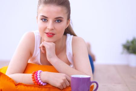 cola mujer: Mujer joven sonriente que miente en un suelo blanco con la almohada.