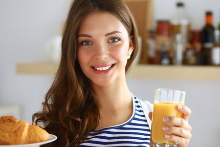 verre de jus d orange: Jeune femme avec un verre de jus de fruits et des gâteaux. Banque d'images