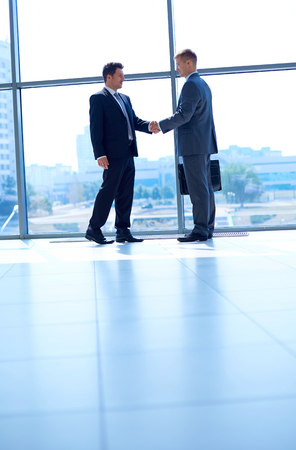 shaking hands: Full length image of two successful business men shaking hands with each other .