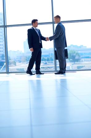 apret�n manos: Imagen integral de dos hombres de negocios exitosos estrechar la mano con la otra.