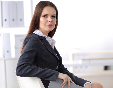 confident business woman: Attractive businesswoman sitting in the office . Stock Photo