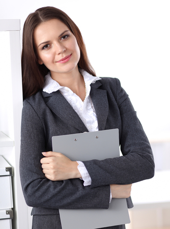 office desk: Attractive businesswoman standing near desk in the office