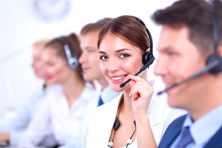 to phone calls: Attractive  positive young businesspeople and colleagues in a call center office Stock Photo