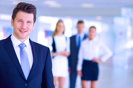 Smiling successful business team standing in office . 스톡 콘텐츠
