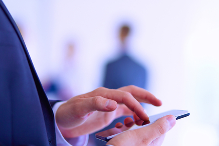 team business: Portrait of young businessman using mobile in office with colleagues in the background .