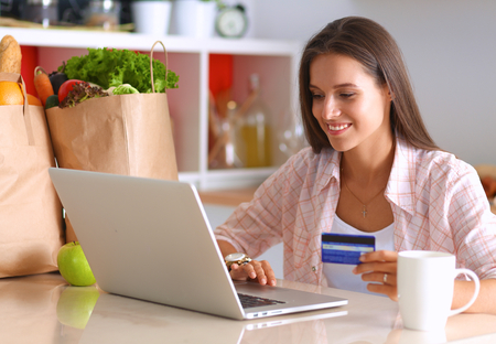 young adults: Smiling woman online shopping using tablet and credit card in kitchen .