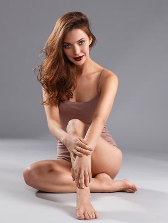 Beautiful barefoot woman sitting on the floor .