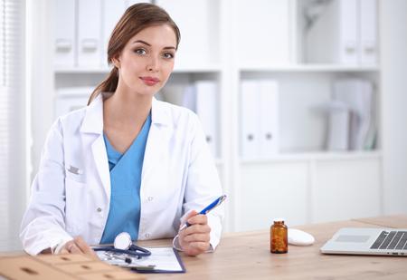 机に座っている美しい若い笑顔女性医師