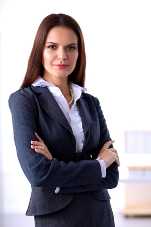 human arms: Portrait of businesswoman standing with crossed arms in office Stock Photo