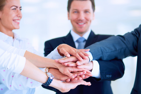 high five: Business people with their hands together in a circle .