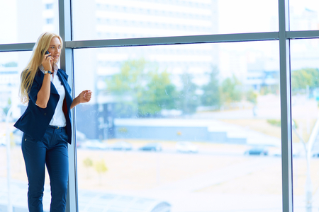 phon: Businesswoman standing against office window holding documents in hand . Stock Photo