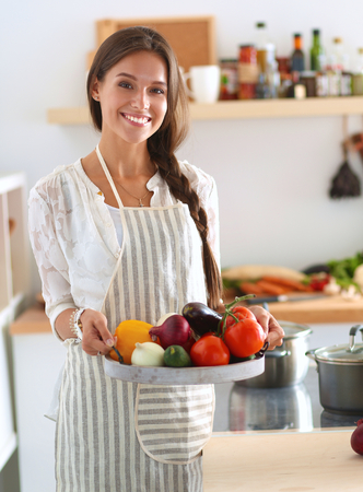 young woman: Smiling young woman holding vegetables standing in kitchen .