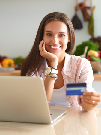 the credit: Smiling woman online shopping using tablet and credit card in kitchen .