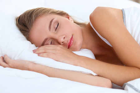 young woman face: Beautiful girl sleeps in the bedroom .