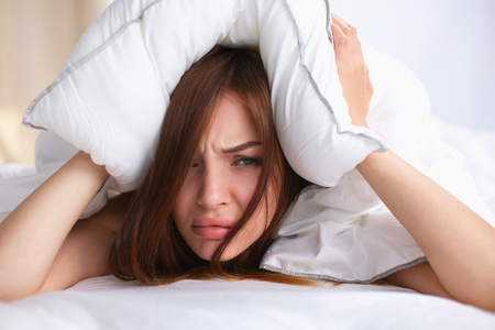 molesto: Mujer acostada en la cama y cerró los oídos con la almohada.