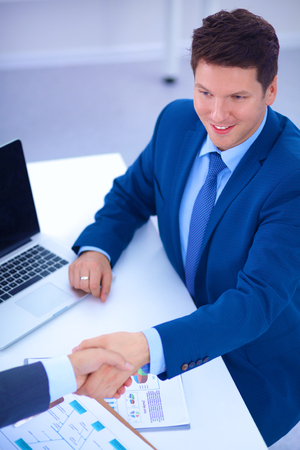 unanimous: Business people shaking hands, finishing up a meeting, in office