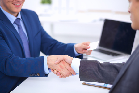 business handshake: Business people shaking hands, finishing up a meeting, in office