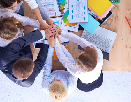 office attire: Business team with hands together - teamwork concepts. Stock Photo