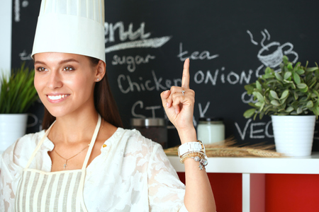 culinary skills: Chef woman portrait with  uniform in the kitchen and pointing up .