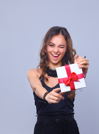 woman in red dress: Young woman happy smile hold gift box in hands, isolated over grey