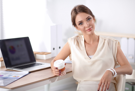 swivel: Beautiful  businesswoman enjoying coffee in bright office, sitting