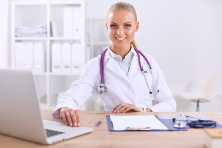 general pediatrician: Beautiful young smiling female doctor sitting at the desk