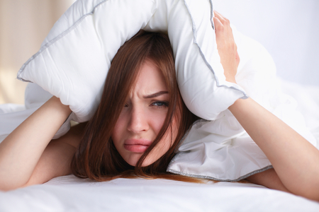 Female lying on bed and closing her ears with pillow. Foto de archivo