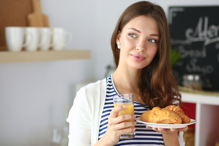 devouring: Young woman with glass of juice and cakes Stock Photo