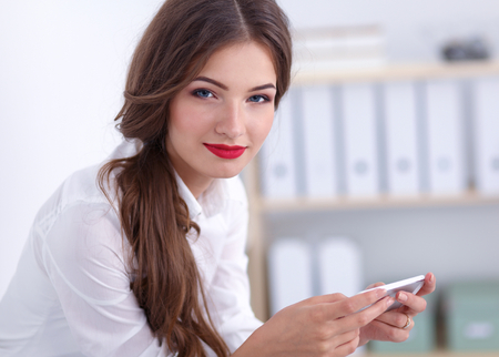 telephone saleswoman: Businesswoman sending message with smartphone in office