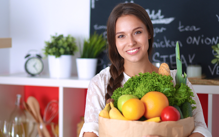 grocery shopping: Young woman holding grocery shopping bag with vegetables . Stock Photo
