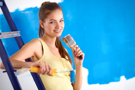 housepainter: Beautiful young woman doing wall painting, sitting on ladder