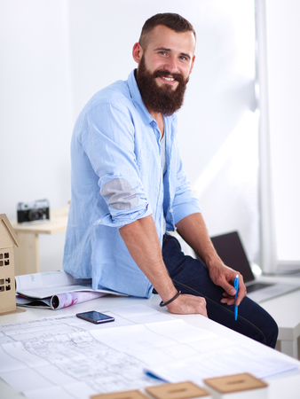 front view: Portrait of male designer with blueprints at desk in office . Stock Photo