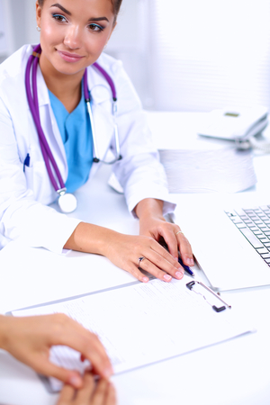 doctor burnout: Doctor and patient sitting on the desk  at office, isolated Stock Photo