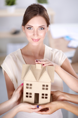 female architect: Portrait of female architect with house model in office. Stock Photo