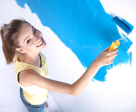 housepainter: Beautiful young woman doing wall painting Stock Photo