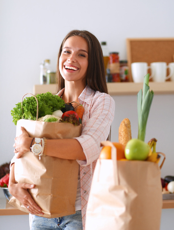 Young woman holding grocery shopping bag with vegetables . Stockfoto