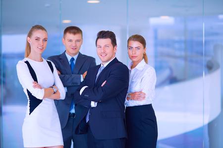オフィスでビジネスの成功のチームに立って笑っています。