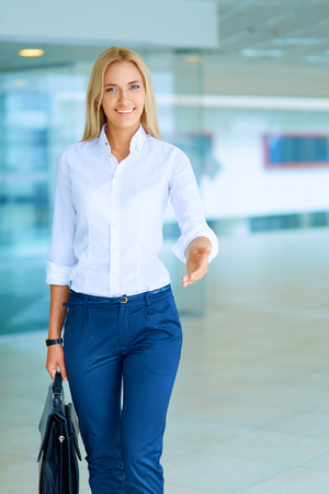 woman in suit: Young business woman ready to handshake standing in office . Stock Photo